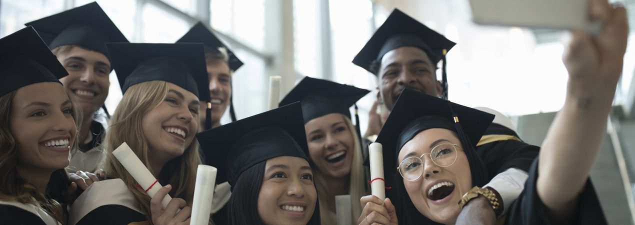 College student graduate friends in caps and gowns taking selfie with camera phone